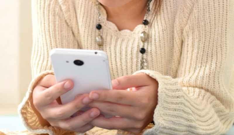 スマホを持つ女性の手の画像